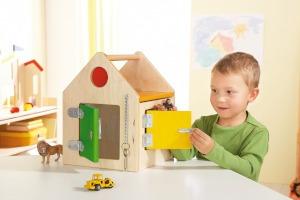 Kind speelt met houten speelgoedhuisje.