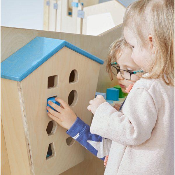 Spelende kinderen die kijken welk blokje in het sorteerhuisje past.